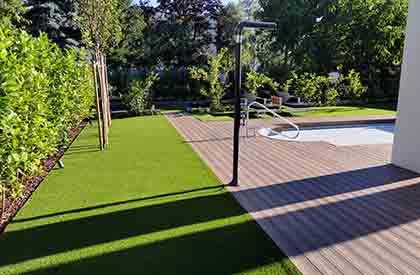 Umjetna trava iz koje rastu voćke i živica te drvena terasa, sve u jednom nivou bez stepenica