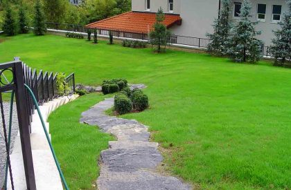 Vrtno stepenište od debelih prirodnih kamenih ploča u travnjaku